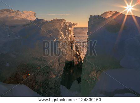 Setting sun shines through the transparent blocks of ice. Beautiful winter landscape in the Lake Baikal.