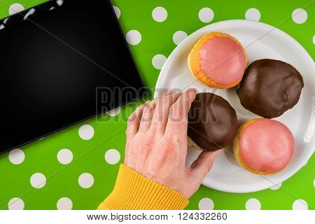 Male hand picking donut with sweet chocolate topping from a plate top view of homemade tasty donuts and digital tablet computer on kitchen table polka dotted surface.