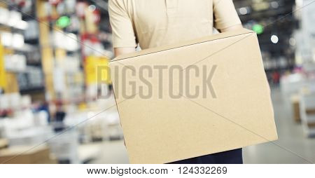 male warehouse worker carrying a carton box of goods in a cash & carry wholesale store.