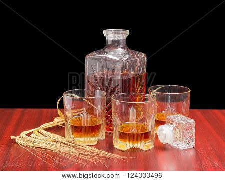 Decanter and three glasses with whiskey stopper from the decanter and several barley spikes on a wooden table on a dark background