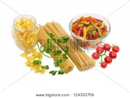 Uncooked dried long pasta two varieties colored spiral pasta and farfalle pasta sprigs of parsley and cluster of cherry tomatoes on a light background