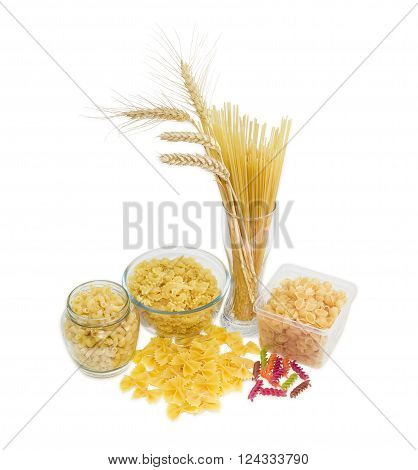Uncooked dried long pasta and wheat spikes in glass other pasta different varieties shapes and colors on a light background