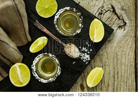 Gold tequila shots on rustic wood background, copy space