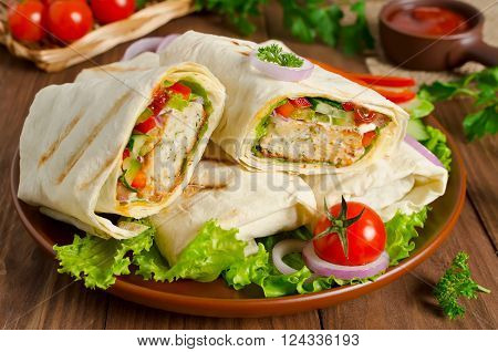 Turkish doner kebab shawarma roll with meat vegetables and pita bread on a wooden background