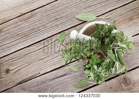 Fresh garden herbs in mortar on wooden table. Oregano, thyme, sage, rosemary. Top view with copy space