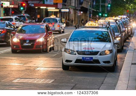 Sydney Australia - November 10 2015: Taxi queued for passengers in Sydney CBD at night. The state of New South Wales is served by a fleet of around 6000 taxis. The industry employs over 22700 taxi drivers.