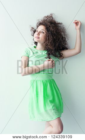 A young girl of Caucasian appearance dancing and dreams of a bright room on a summer day. Wavy curly hair and green dress. Rest and be happy.