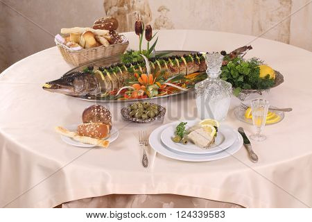 pike baked in the oven served with lemon and olives and a carafe of vodka
