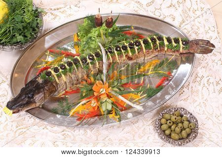 pike baked in the oven served with lemon and vegetables