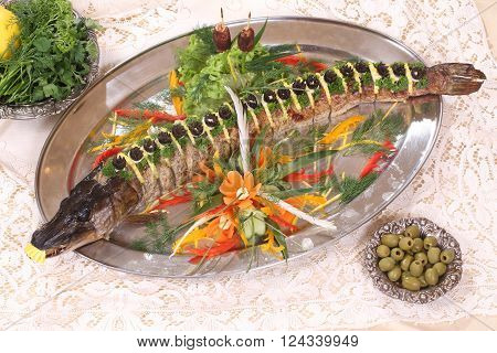 pike baked in the oven served with lemon and olives and vegetables