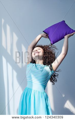 Portrait of a beautiful young girl with brown curly hair. Play with pillows. To arrange a pillow fight. Fun and joy. Purple pillow in the hands of a girl in a blue dress.