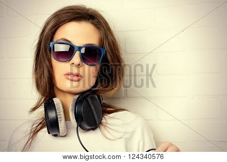 Modern young woman enjoys the music on headphones. Youth style, leisure.