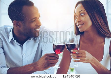Celebrating their special date. Beautiful young African couple sitting close to each other and holding wineglasses
