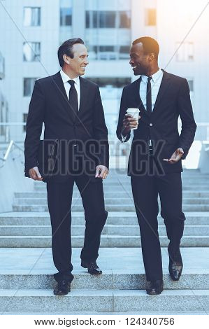 Discussing business. Full length of two cheerful business men talking while moving down by staircase