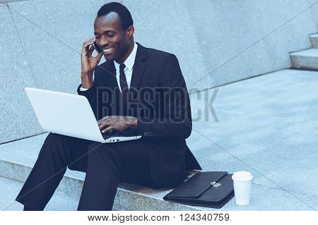 Doing business everywhere. Cheerful young African man in formalwear talking on the mobile phone and working on laptop while sitting on outdoors staircase