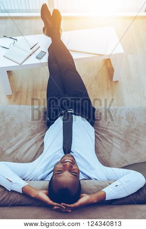 Carefree daydreamer. Top view of happy young African man in formalwear lying on the couch with his legs on a desk and hands behind head