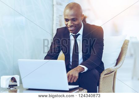 Working with pleasure. Cheerful young African businessman using his laptop while sitting at the restaurant