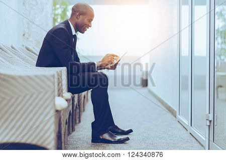 Checking his business schedule. Side view of cheerful young African businessman working on digital tablet while sitting on the chair