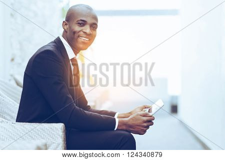 Confident businessman. Side view of cheerful young African businessman working on digital tablet and smiling at camera