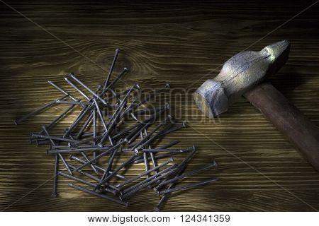 Hammer and nails on dark wood table
