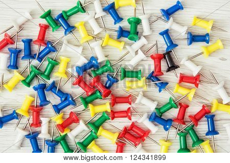 Background of coloured thumbtacks - office push pins. Office supplies.