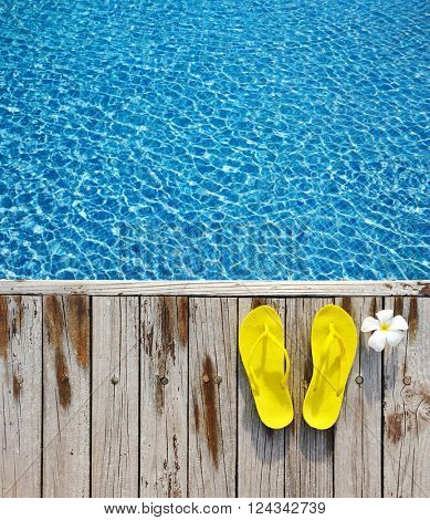 Yellow flip-flops by a swimming pool