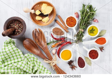 Herbs, condiments and spices on wooden background. Top view