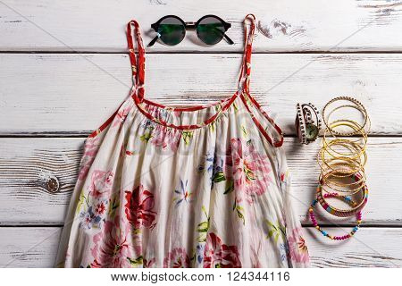 Flax sarafan and chameleon sunglasses. Female clothing on the table. Classy summer style for women. Look good and feel comfortable.