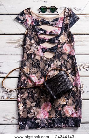 Deep neckline dress and sunglasses. Stylish evening clothes on shelf. Dark dress with black purse. Become the center of attention.