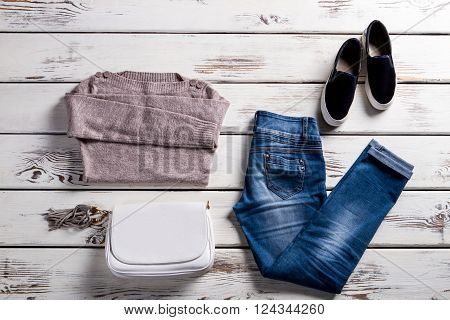 Jeans with sweatshirt and shoes. Young woman's outfit on showcase. Simple autumn clothes with handbag. Lady's clothing for spring.