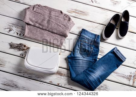 Sweater and slip-on shoes. Female autumn outfit on display. Clothing for young stylish women. Selection of woman's spring clothes.