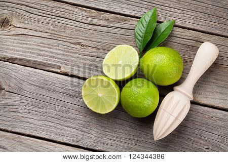 Fresh limes and juicer on wooden table. Top view with copy space