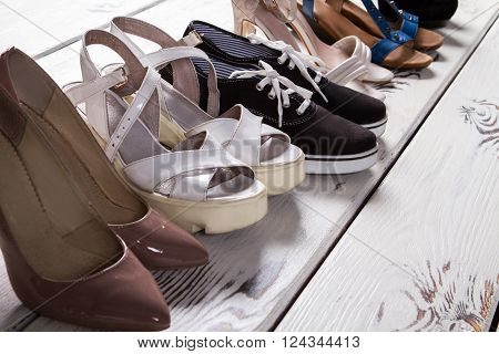 Lady's different shoes in row. Woman's footwear on boutique floor. Summer shoes of high quality. Luxury shoes and simple keds.