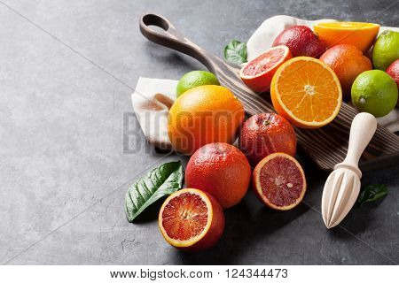 Fresh citruses on dark stone background. Oranges and limes. View with copy space