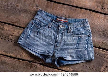 Light denim shorts on floor. Shorts on old wooden floor. Classic garment on wooden showcase. Garment on aged wooden background.