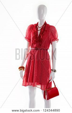 Bright red dress on mannequin. Female mannequin in fashionable dress. Short ripple dress for summer. Woman's red outfit with accessories.