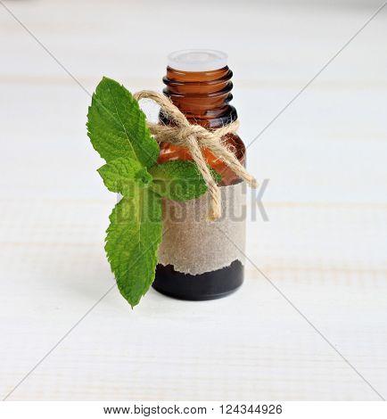 Essential mint oil. Mint fresh herb, essence bottle.