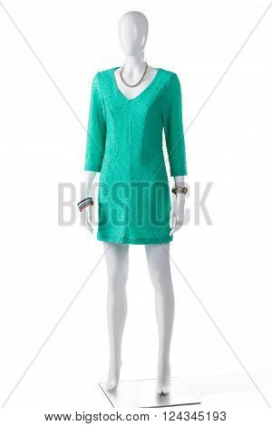 Casual turquoise dress on mannequin. Female mannequin in turquoise dress. Lady's bright-colored casual clothing. Long sleeve summer garment.