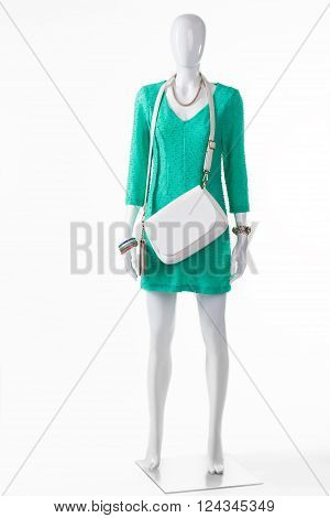 White handbag with turquoise dress. Female mannequin wearing white purse. High-quality leather accessory. Woman's clothing and handbag.