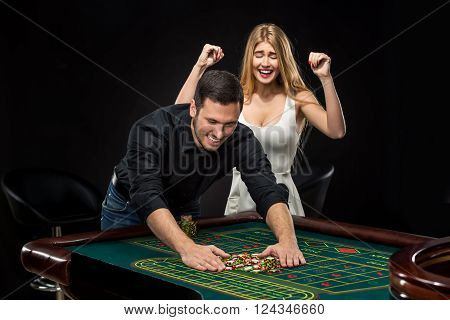 Young couple celebrating win at roulette table in casino,  gambling chips taken by hands men. Addiction to the gambling