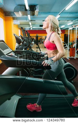 Girl walking on treadmill. Active girl in gym walking on treadmill. Young blonde cardio activity in gym.