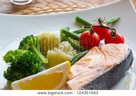 Salmon steak and steamed vegetables, served on a wooden background. Lenten  healthy food. Top view on dietary fish dish with salmon and vegetables