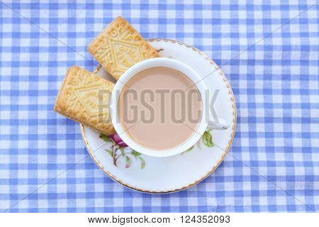 Milky tea with two unbranded custard creams on a gingham tablecloth ** Note: Visible grain at 100%, best at smaller sizes