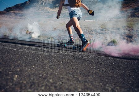Cropped image of young woman skateboarding on a road. Skate board with colored smoke grenade.