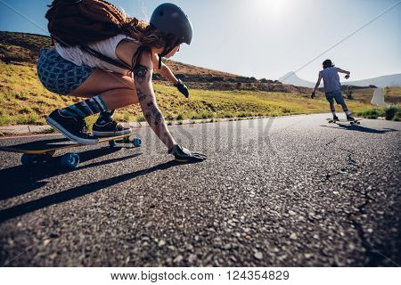 Young woman skating with her friend in background. Young people longboarding on rural road on summer day.