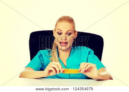 Shocked and scared female nurse or doctor sitting behind the desk and holding packet of pills