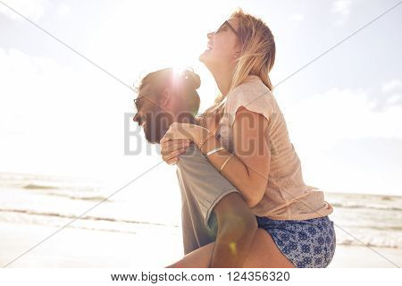 Side view portrait of young man carrying his girlfriend on his back at the beach. Man piggybacking girlfriend at seashore on sunny day.