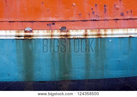 rusty metal bow of old fisher boat hull in orange blue and white