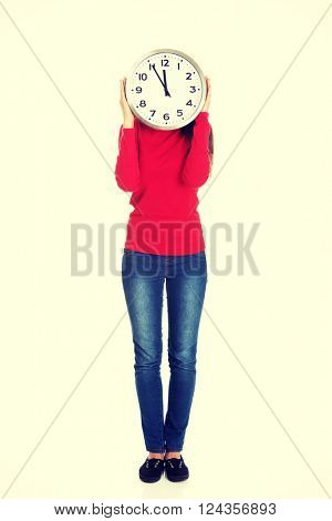 Woman hiding behind a clock.