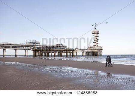 Den Haag, Netherlands, 27 march 2016: couple walks on empty morning beach near pier of scheveningen